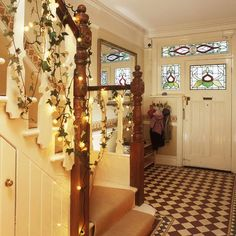 Christmas hallway with chequered floor tiles, fairy lights and ivy garlands