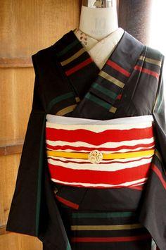 風合いのある黒の地に、赤と黄色と緑のカラフル横段ボーダーが織り出されたシンプルモダンな正絹紬袷着物です。