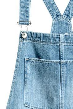 Jardineiras em ganga: Jardineiras em ganga lavada com pormenores de muito desgaste. Têm alças ajustáveis, botões nos lados e pernas afuniladas. Bolso no peito, bolsos laterais e bolsos traseiros.