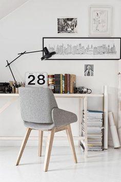 Escritorio con mesa de madera color natural y silla con base de madera y silla y respaldo de tela color gris. Sobre la mesa una lámpara flexo de color negra.