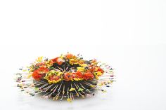 Colors that pop, that's what Alex Segura likes in his floral design! In his 'Summer in Rio' flower arrangement he used 'Eychenne All Black' foam by Oasis, which makes an even sharper contrast with the bright colored gerberas 'Anita' and 'Antique', freesia, Physalis and Viburnum. Fun cocktail sticks add to a summery feeling!