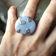 Il materiale nobile e in primo piano è il calcedonio con la sua forma ovale è piatta. La montatura in argento è costruita per dare rilievo alla pietra che primeggia in questo anello, come una roccia che si aggrappa al suo 'pezzo forte'. Ruoli invertiti