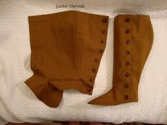 Part II: Fitted Gaiters: These fitted gaiters are made from two layers of golden brown canvas.  Top and bottom edges are turned between the layers for a clean appearance inside and out.  They button closed.  This image shows the outside of both gaiters, one buttoned and the other open.