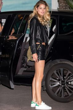 Doutzen Kroes wears leather shorts and a leather jacket with Adidas Stan Smith Sneakers