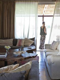 Living luminoso de una casa de fin de semana con mesa ratona de timbó sobre una base de hierro, sillones en color gris y crudo, y grandes ventanales con cortinas marrón que conectan con el exterior.