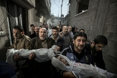 The bodies of two-year-old Suhaib Hijazi and his elder brother Muhammad, almost four, are carried by their uncles to a mosque for their funeral, in Gaza City.