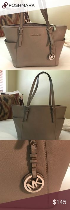 "Michael Kors Jet Set Tote Michael Kors Large Jet Set Tote. It's grey with silver hardware. The bag is like brand new and barely used. Very small stain on back lefty side that is also pictures up close.  Dimensions: 17"" W x 11"" H x 5"" D Michael Kors Bags Totes"