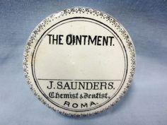 GDL Auctions - Toowoomba (65) - 16th February 2013 - Lot: 745 - Pot Lid - small size 'J Saunders, Chemist & Dentist, Roma - The Ointment' fancy floral border. Some glaze discolouration, small flakes & hairline to base of flange. 6cm diam. Condition: Good. #Bottles #PotLids #MADonC