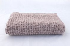 This rectangular hand knitted blanket has been made with an intricate basket-weave stitch, using a flecked beige yarn. It has a crochet border executed in the same yarn. This would make a very lovely baby blanket, but might also be a small throw to put over an armchair or your knees, on a cold winters night.. Yarn: Hayfield Bonus Aran Tweed, 6 % Viscose 20% Wool, 74% Acrylic Colour: Sagewood  Size: Approximately 107 x 103 cm ( app 42 x 43 inches )  Its ready for immediate shipping. This item…