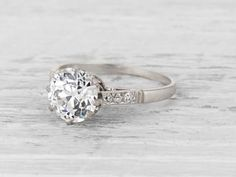 Antique Edwardian engagement ring made in platinum and centered by a GIA certified 2.38 carat J color VS2 clarity old European cut diamond. Accented by 6 single cut diamonds.Circa 1915 The center stone on this lovely ring is a show stopper! This ring works well paired with a band or on it's own. Diamond and gold mining has caused devastation in areas such as Africa, wreaking havoc on delicate ecosystems and communities. Choosing to go vintage, you are eliminating the need for more minin...