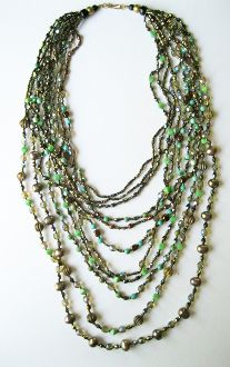 One of my earlier works, this is a multi strand gaggle with varying lengths. It's mostly copper tones accented with various shades and shapes of green beads, each strand a different composition.