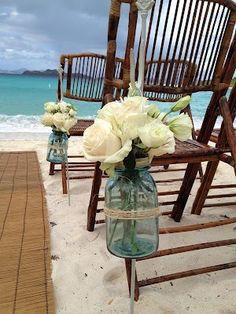 White roses in mason jars at the ocean