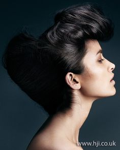 2012 black shiny updo hairstyle    Long black hair was prepped with mousse and roughly blow-dried to add volume and movement. Hair was then divided into two horizontal sections from ear to ear. The lower section was backbrushed all over and wrapped around padding into a classic chignon shape. The top section was then rolled around into a large loop and pinned in place.     Hairstyle by: Emiliano Vitale  Hairstyle picture by: Paul Scala  Salon: E Salon  Location: Australia