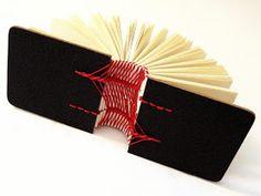 pretty black and red book with interesting spine stitch - variation on the caterpillar stitch? - estudo para encadernação artesanal from Canteiro De Alfaces