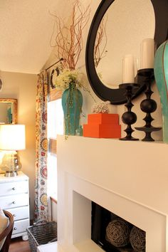 mantel decor- large balls in fireplace. curtains. turquoise and orange color pops