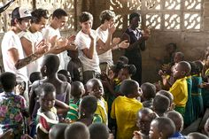 1D performing with children in Ghana
