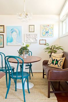 Gallery wall in white dining space with brown bench, yellow patterned pillows and turquoise chairs