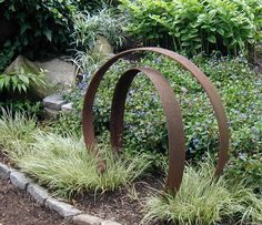 Old rusty farm parts as garden sculptures
