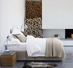 neutral bedroom with white walls, fireplace, wood stack and concrete floors