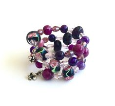 This gorgeous memory wire bracelet is in rich and sweet tones of pink, lilac, plum and purple. Its a real piece of wearable art!  I used lamp work beads in a deep eggplant shade, lilac and pink crystals, pink glass stones, agate beads in a plum marbled tone and deep berry shade, and pretty murano floral beads. At each end of the bracelet I added pewter fleur de lis charms - they seem to add to the regal feel of this bracelet!  Please refer to my shop policies for more information. Dont…
