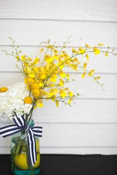 Super cute striped ribbon with white and yellow flowers. Complete the summer look with lemons in the vase.