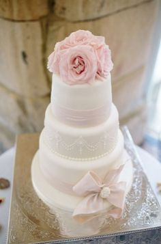 Sweet three-tier white wedding cake with blush pink flower topper and ribbons