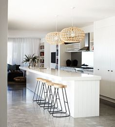 """Coastal kitchen - Smaller versions of the cane pendant featured in the dining area combine with timber panelled kitchen cabinetry by Haughey Group to add to the beachy feel. """"We didn't want slick, smooth surfaces so this helped bring in texture,"""" the homeowners say. The Sled bar stools are from Les Interieurs."""
