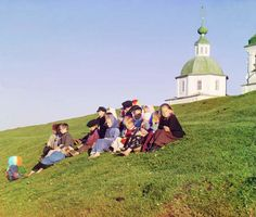 Sergei Mikhailovich Prokudin-Gorskii. A Group of Children, 1909. Children sit on the side of a hill near a church and bell-tower in the countryside near White Lake, in the north of European Russia.