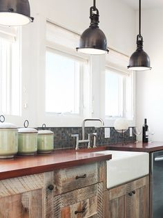 i loved the use of natural and artificial use of lighting in this picture. small windows but there are many of them and small light shades on the top in the centre of the kitchen.