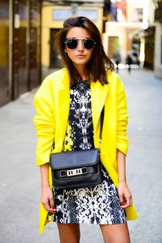 Bright yellow coat paired with a black and white printed dress