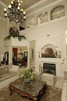 I love ABSOLUTELY EVERYTHING about this room! The ledge leading to the dining rm, the arches in the loft area, the niche fireplace, the dining nook, the iron chandeliers.  Super like this design!