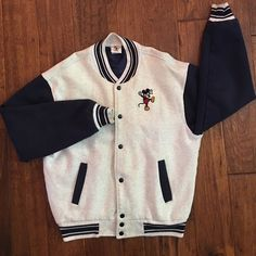 Vintage, rare find Disney store Letter Jacket Snaps up the front with navy blue snaps. All gray with navy arms and navy trim. Mickey Mouse on front left of front. Large red M with Mickey Mouse sitting on top smiling on the back of jacket. This is vintage. They do not make these anymore. I wore it over 20 years ago and it's been stored nearly ever since. It's time to sell. Rare find. Mickey & Company Jackets & Coats