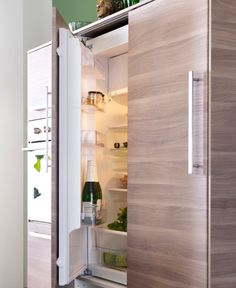 Integrated fridge with open door revealing champagne bottle and glass jars