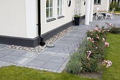 Exempel på hur en stenlagd gång runt huset kan se ut. Avslutas med kantsten mot gräsmattan.