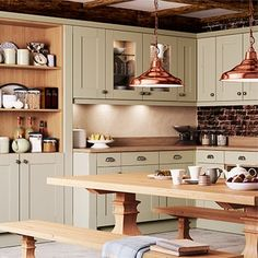 Green cupboards and wooden worktop and copper pendant lights...nice, calming