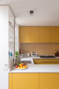The existing oak floor of a house in London has been stained dark, creating a contrast with the bright yellow kitchen units and custom orange splashback tiles.