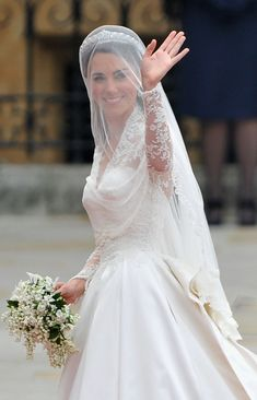 Catherine Middleton waves to the crowds as her sister and Maid of Honour Pippa Middleton holds her dress before walking in to the Abbey to attend the Royal Wedding of Prince William to Catherine Middleton at Westminster Abbey on April 29, 2011 in London, England.