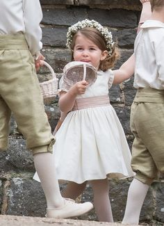 Princess Charlotte wore a cream sash dress and scattered confetti petals from a basket