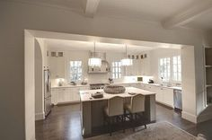 U shaped kitchen with floor to ceiling cabinets. Like the open glass at top of cabinets.