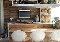 A varanda gourmet é a queridinha da casa, assinada pela designer de interiores Carol Lovisaro, em parceria com a arquiteta Fernanda Lovisaro. Toda revestida de peroba de demolição rústica, ela ganha o colorido das cadeiras de estilos diferentes