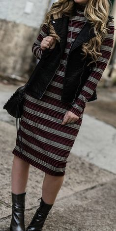 Edgy midi dress outfit styled with  a leather vest, metallic booties, and black round sunglasses