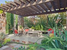A stunning pergola draws you into the shade of this concrete patio. With wood and stone construction, the pergola is a rustic accent to the Mediterranean-style chandelier and lush landscaping. Timeworn patio furniture creates a cozy seating area with bright red pillows.