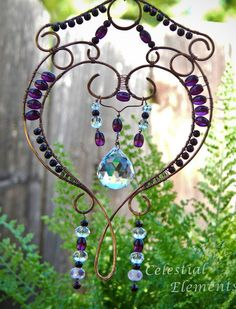 It is a Sun Catcher for hanging in window. Has copper wire bent into a heart shape. Beads wrap frame and crystal is suspended in center.