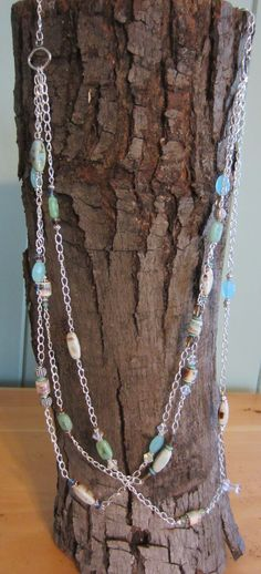 An absolutely gorgeous necklace if I do say so myself! 3 strands of silver chain interspersed with pretty green and blue beads, a variety of porcelain beads of brown, blue and green design on off white, plus a mixture of silver, Swarovski, and glass beads. One of my favorites!