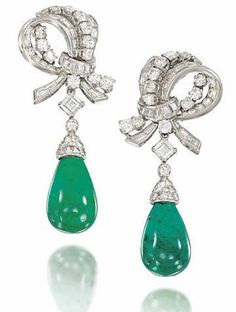 A Pair of Emerald and Diamond Ear Pendants, probably by Bulgari. Photo Christie's Image Ltd 2013    Of scrolling design, each composed of a circular and baguette-cut diamond surmount, to a single square-cut diamond spacer, suspending a polished emerald drop below, with diamond set cusp. Estimate: $67,905 – $82,995