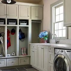 Mudroom in Laundry Room with built-in open lockers. Perfect individual cubbies for storing jackets and sporting equipment. Laundry room with front loading washer and dryer and a sink for hand washing and pre-treating stains.
