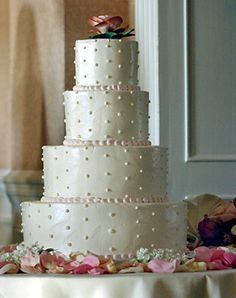 White Wedding Cake with Swiss Dots. The couple's buttercream-frosted cake was decorated with ivory Swiss dots, a pale pink icing border and a single pink bloom.