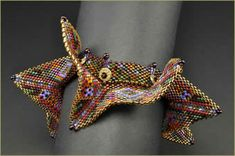 """Barbara Briggs - """"Delica beads in vivid shades convey energy and excite the eye while petite disks of bronze metal clay topped with Swarovski Lochrosen crystals and metallic bronze 11/0 seed beads embellish the MRAW band. I'm pleased with this piece – it has a feeling of Wings gone wild on LSD! I've titled this piece """"Azteca""""."""""""