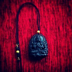 Worldwide Inspirations    A hand crafted pendant of an obsidian Buddha Amulet binded  with spinel minerals and gold plated silver.
