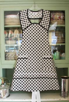 Cute Homemade Apron in black and white check and rick rack. Hanging on a big old Hoosier cabinet filled with antique stoneware and chintz china.